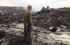 Armed pro-Russian separatist stands at a site of a Malaysia Airlines Boeing 777 plane crash in the settlement of Grabovo in the Donetsk region