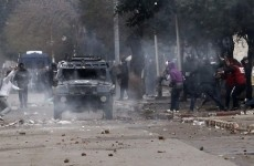 Protesters run as police fire tear gas during clashes in Baraki, near Algiers