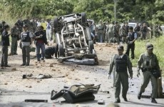 Police officers survey the site of a bomb attack in Yala province